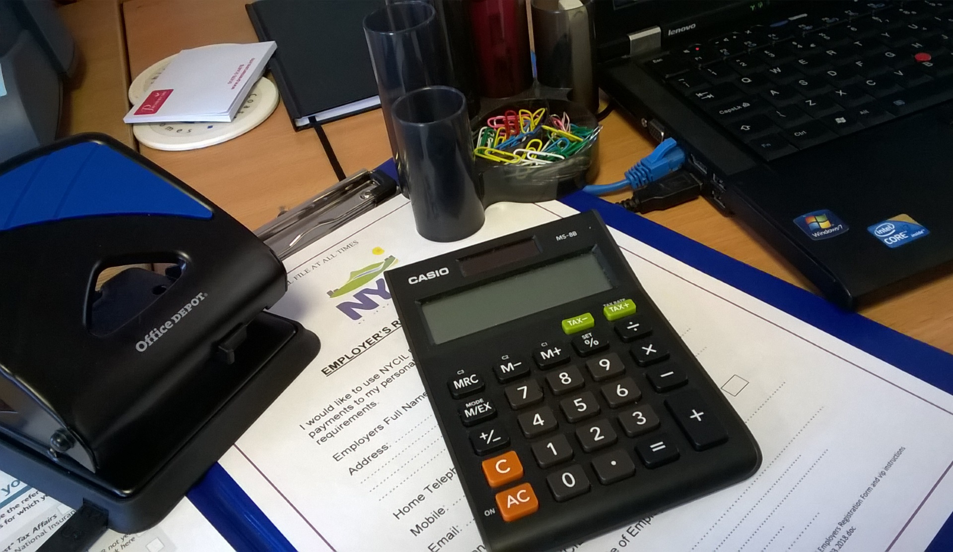 Payroll themed image of a messy desk with a laptop, calculator, clipboard ect.